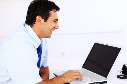 Cheerful business man typing on a laptop computer.